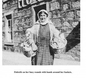 Fishwife on her busy rounds with hands around her baskets.